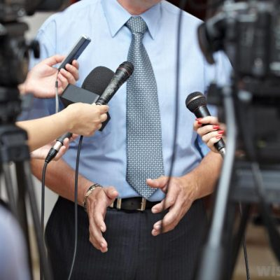 man-in-blue-tie-and-shirt-at-microphones